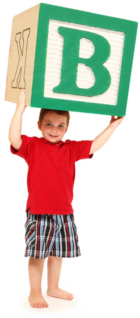 Little boy holding a large alphabet block